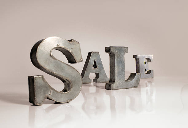 Sale metal letters on white surface stock photo