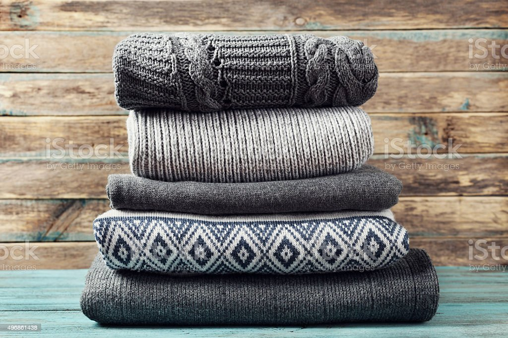 Sale of knitted winter clothes on wooden background, sweaters, knitwear stock photo