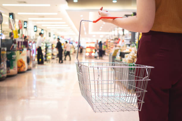 sale, shopping, consumerism and people concept - woman with food basket in supermarket stock photo