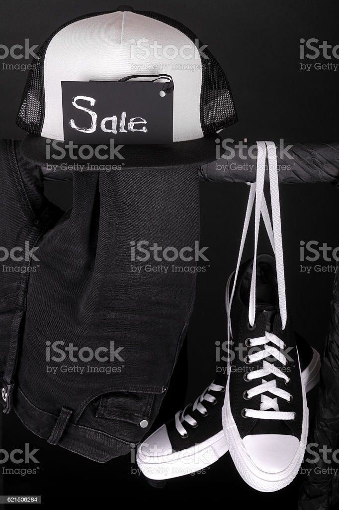 Sale sign. Black and white sneakers, cap  pant, jeans hanging photo libre de droits