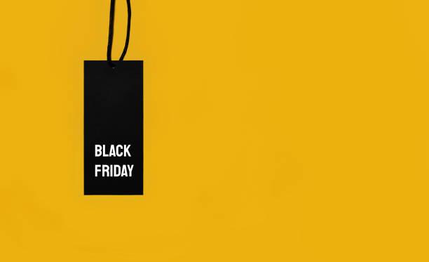 sale tag with black friday inscription on yellow background. - black friday zdjęcia i obrazy z banku zdjęć
