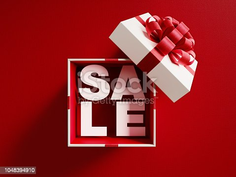 Sale text is coming out of a white gift box tied with red ribbon on red background. Horizontal composition with copy space. Directly above. Great use for Christmas and Valentine's Day related gift concepts.