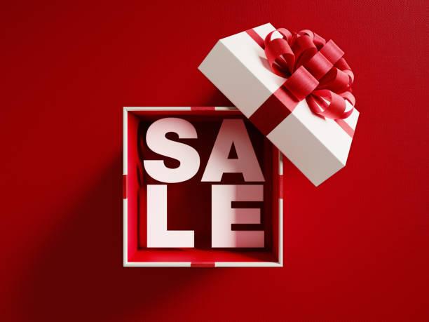 verkauf-text aus einer weißen geschenkbox gebunden mit rotem band - günstige weihnachtsgeschenke stock-fotos und bilder