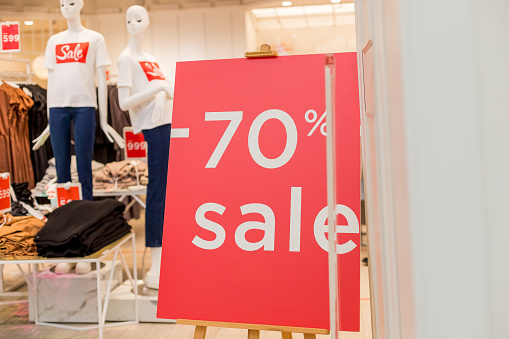 Sale up to 70 percent red sign. Red circle with sale up to seventy percent inscription sticked on the store window