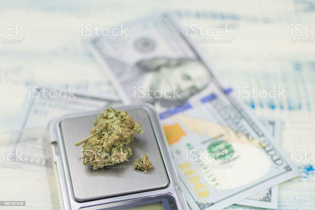 Sale, weighing of marijuana. Bud of marijuana on a jewelry scales against the background of dollars. stock photo