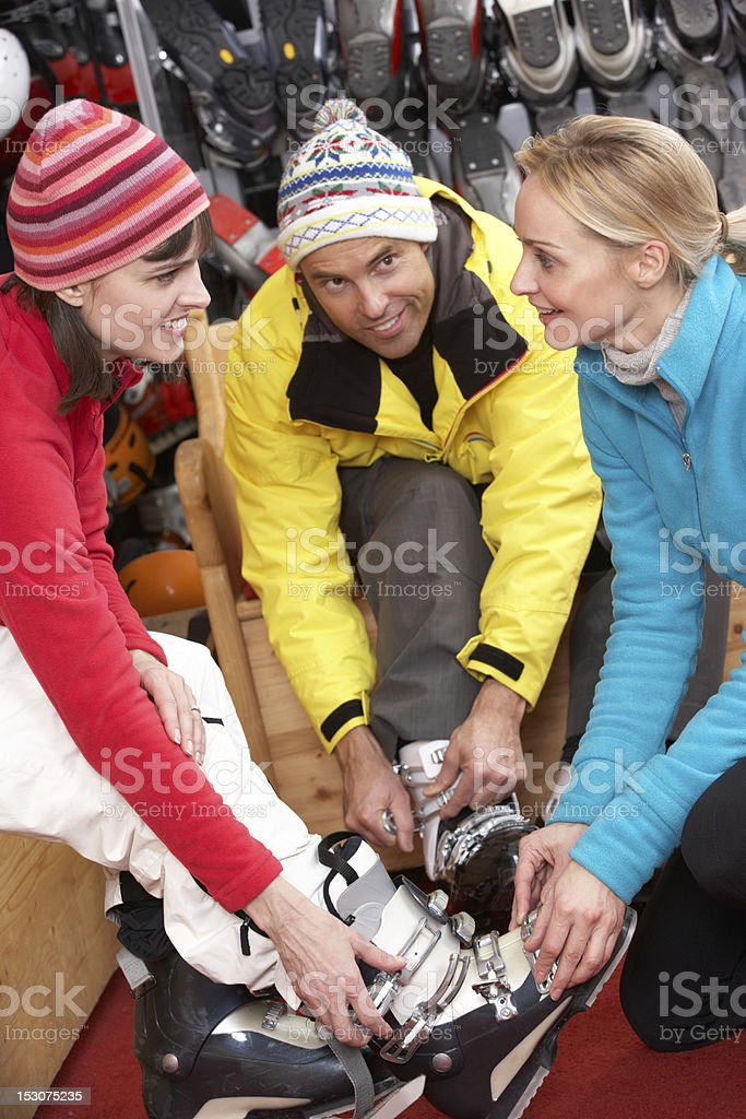 Sales Assistant Helping Couple To Try On Ski Boots stock photo