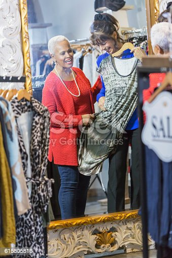 istock Sales assistant helping customer in clothing store 615805816