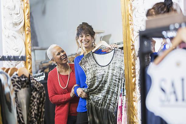 sales assistent hilft kunden in bekleidungsgeschäft - 70 jahre kleidung stock-fotos und bilder
