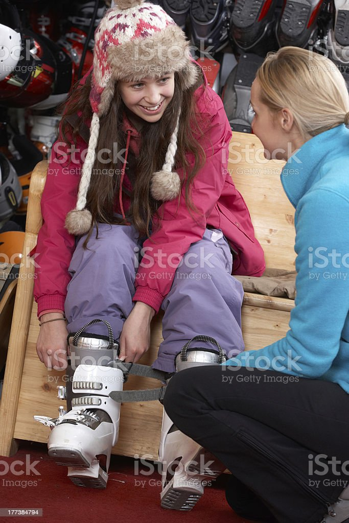 Sales Assistant Helping Teenage Girl To Try On Ski Boots stock photo