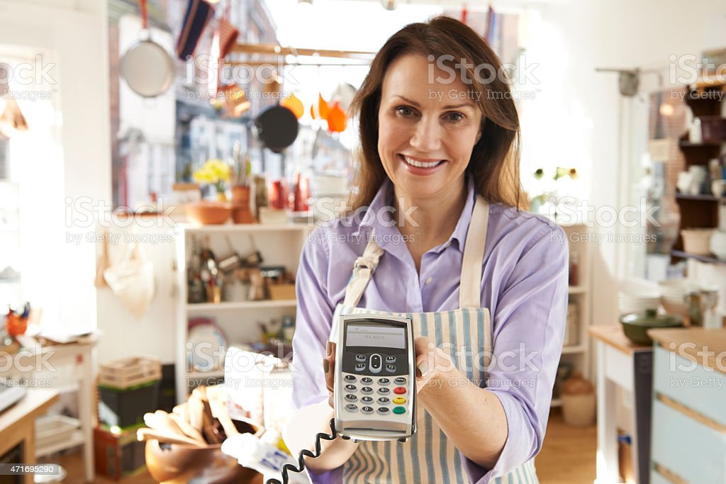 Sales Assistant In Homeware Store With Credit Card Machine stock photo