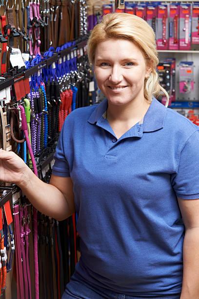 Vendeur de magasin pour animaux de compagnie avec chien en laisse affichage - Photo