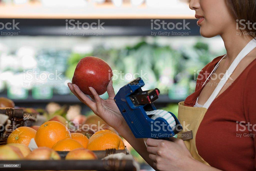 sales assistant pricing an orange stok fotoğrafı