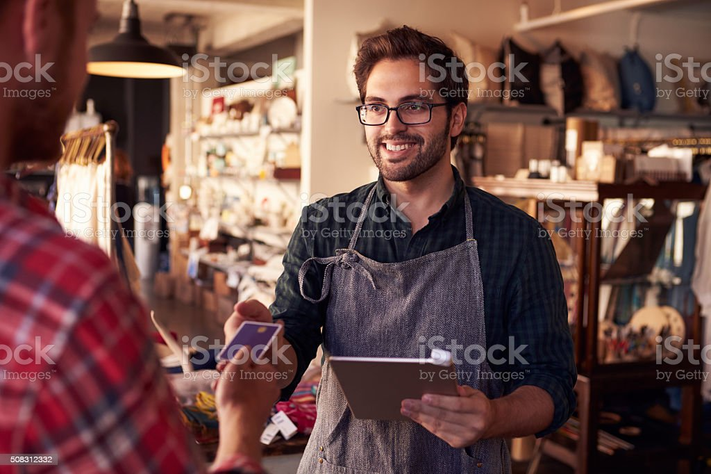 Sales Assistant With Credit Card Reader On Digital Tablet stock photo