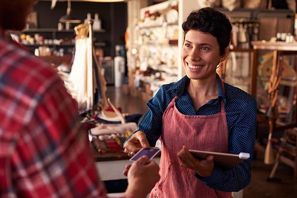 セールス担当アシスタントにクレジットカードリーダデジタルタブレット - 小売販売員 ストックフォトと画像