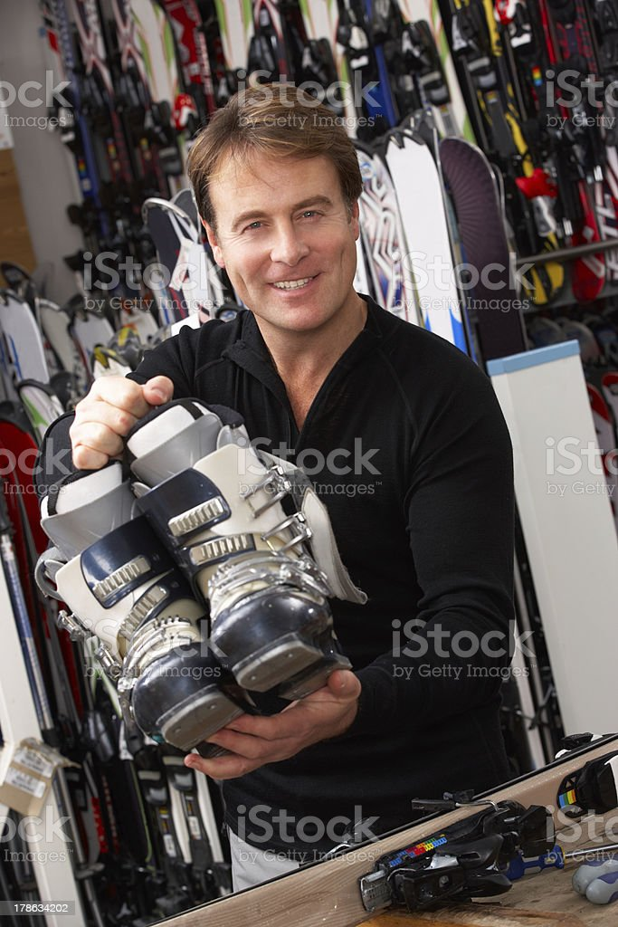 Sales Assistant With Ski Boots In Hire Shop stock photo