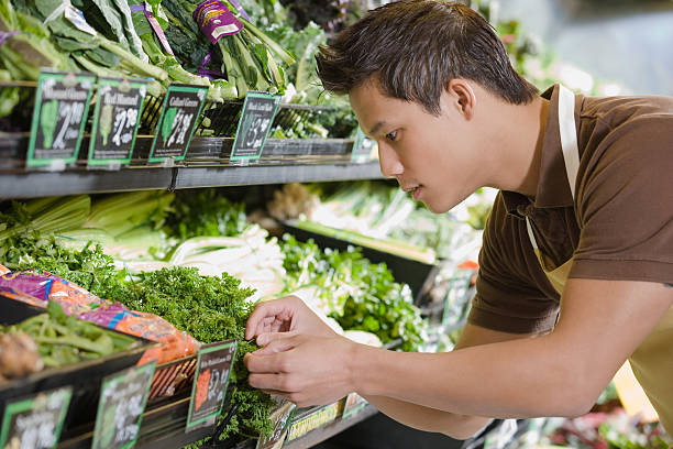 Sales assistant working in a supermarket Sales assistant working in a supermarket produce aisle stock pictures, royalty-free photos & images