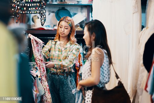 Sales clerk assisting a customer in a thrift store in Japan