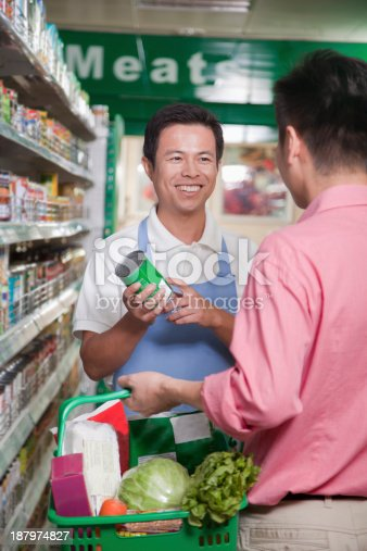 istock Sales clerk assisting man in supermarket, Beijing 187974827
