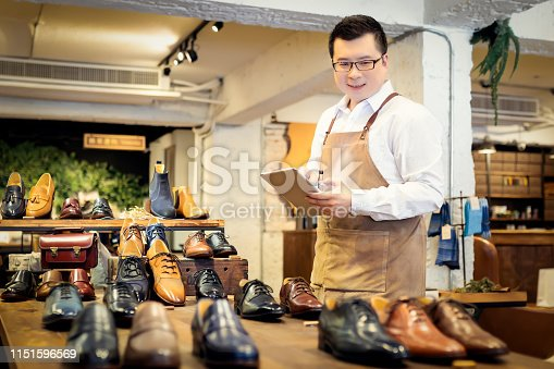 istock Sales clerk checking shoes in boutique 1151596569