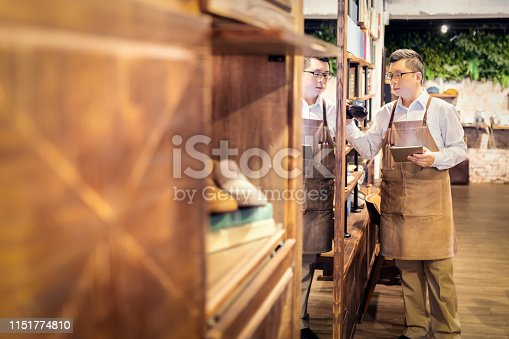istock Sales clerk checking shoes in boutique 1151774810
