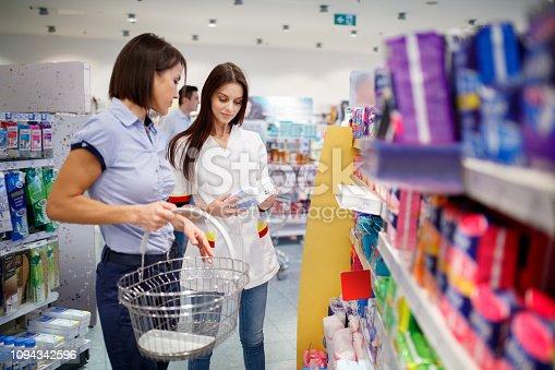 Sales clerk helping customer with shopping basket choose sanitary pads in pharmacy