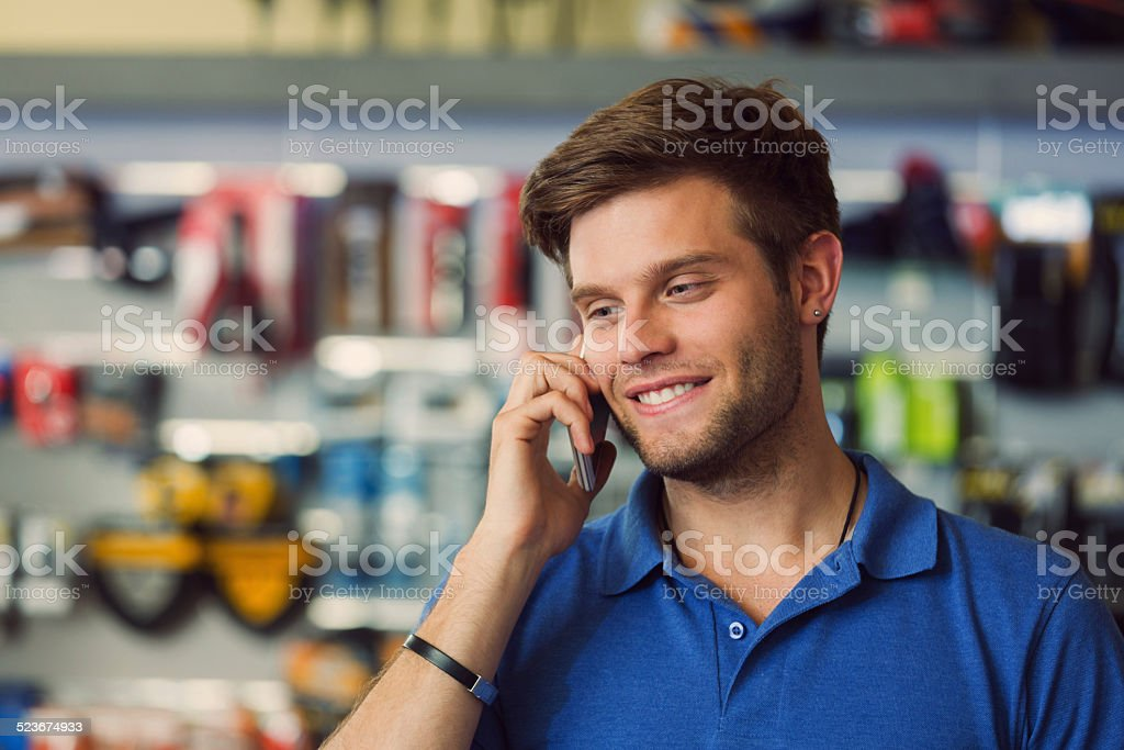 Sales clerk on phone in bike shop Close up of sales clerk of sports store talking on cell phone. 20-24 Years Stock Photo