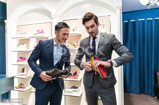 Young handsome seller in suit showing to handsome  Asian customer leather shoes in shoe store