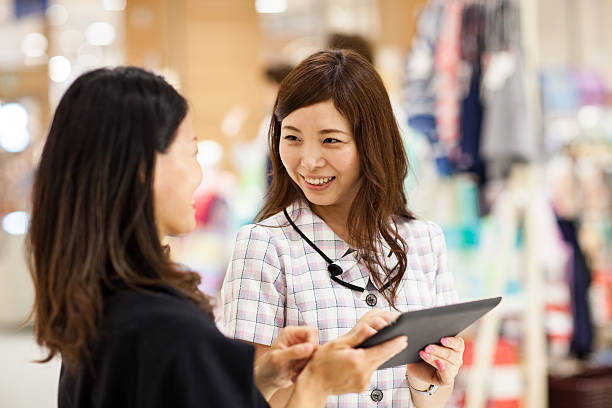 Sales clerk using a digital tablet to assist customer A sales clerk using a digital tablet to assist customer with shopping. sales clerk stock pictures, royalty-free photos & images