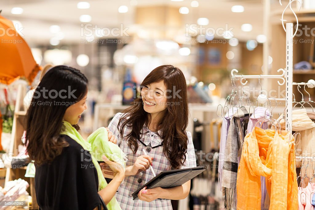 Sales clerk using a digital tablet to assist customer stock photo