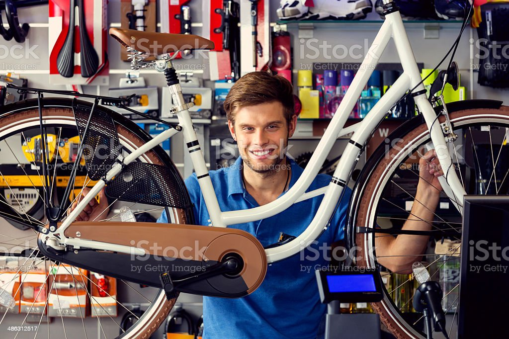 Sales clerk with a bicycle Portrait of young sales clerk in a bike store, holding a bicycle and smiling at camera. 20-24 Years Stock Photo