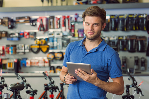 Sales Clerk With Digital Tablet In Bike Shop Stock Photo - Download Image Now