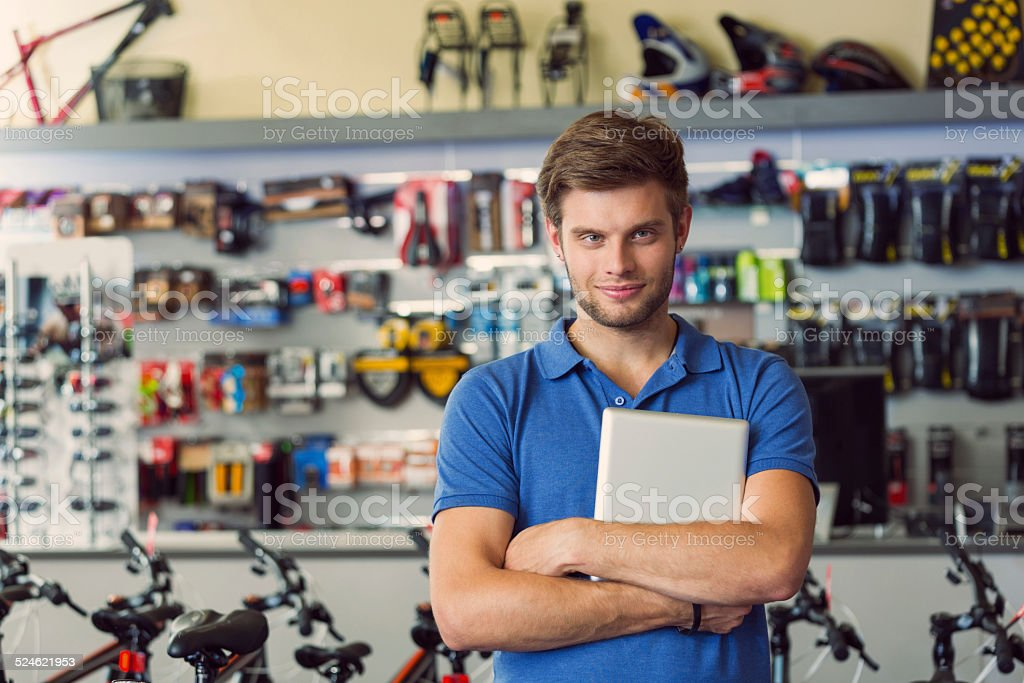Sales clerk with digital tablet in bike shop Portrait of sales clerk of sports store, standing with digital tablet and smiling at camera. 20-24 Years Stock Photo