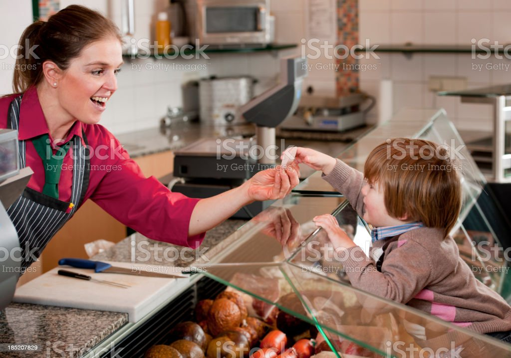 Sales executive giving sausage to toddler royalty-free stock photo