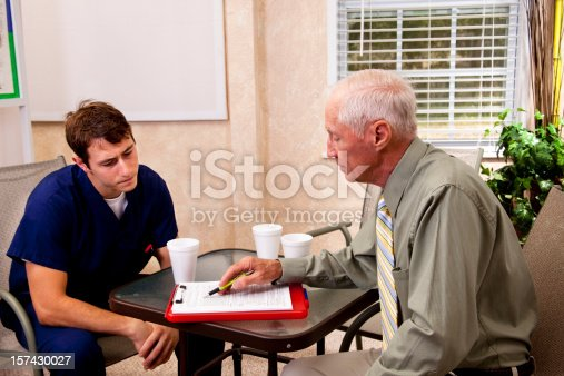 Sales representative or insurance agent in a hopsital office lounge with paperwork, documents and coffee.  He is talking to a doctor.