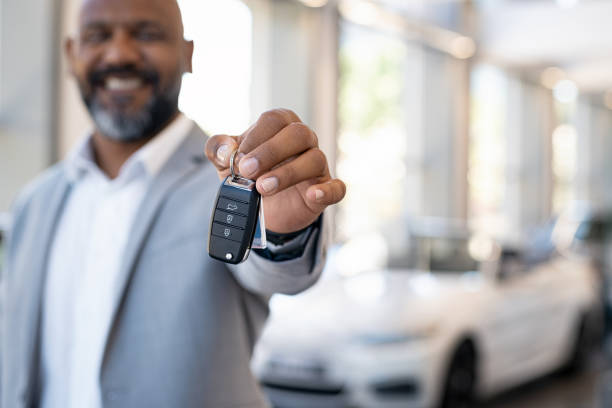 Sales man with car keys Smiling salesman holding new car keys in car showroom. Businessman is suit in car showroom showing car keys. Closeup hands of african man holding keys on car rental salon with copy space. car key stock pictures, royalty-free photos & images