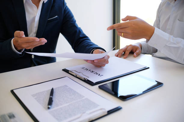 Sales manager giving advice application form document, considering mortgage loan offer for car and house insurance. stock photo