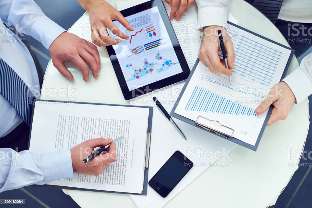 Sales managers preparing report together stock photo