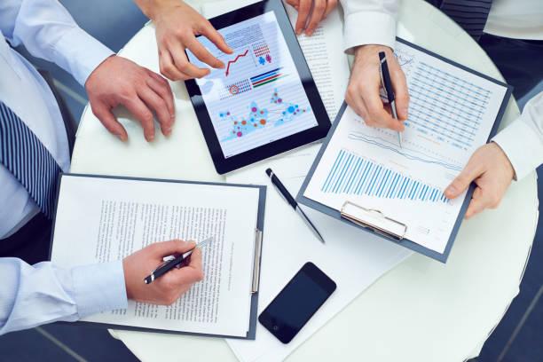 sales managers preparing report together - rapporto finanziario foto e immagini stock