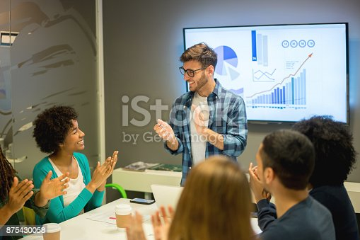 1007383644 istock photo Sales people at a business meeting applauding themselves for reaching the annual sales 875430058