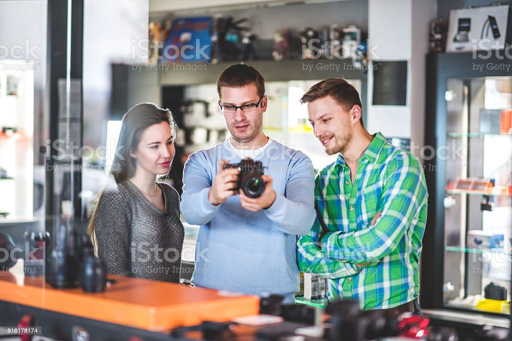 Sales Person Showing Digital Camera Stock Photo - Download Image Now -  iStock