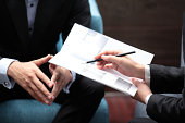 Close-up of businesswoman's hand holding a pencil pointing at a brochure with a businessman in meeting.