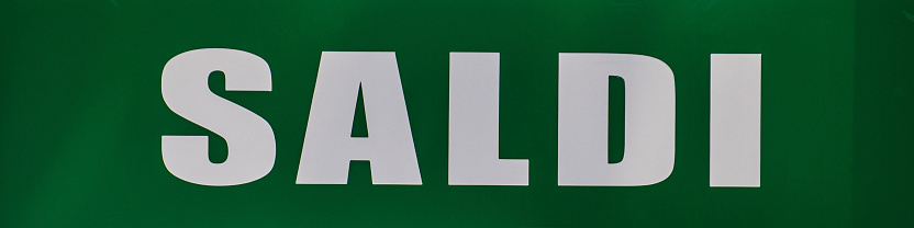 sales sign exposed on a shop window green background white writing