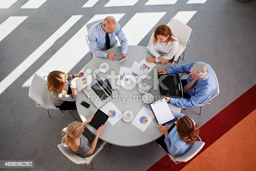High angle view of business people discussing in a meeting while sitting at conference table. Businesswomen and businessmen using digital tablet and computer while analyzing financial data.  Aerial shot taken from directly above the table.