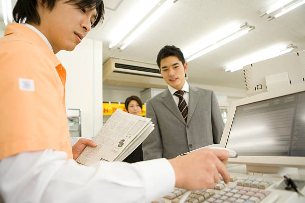 salesclerk at convenience store and young man shopping stock photo