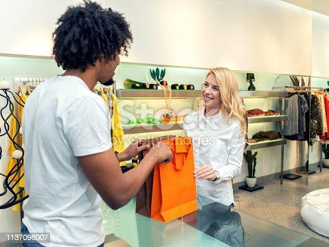 istock Salesclerk handing merchandise to customer 1137096007