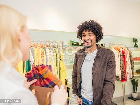 istock Salesclerk handing merchandise to customer 1144637959