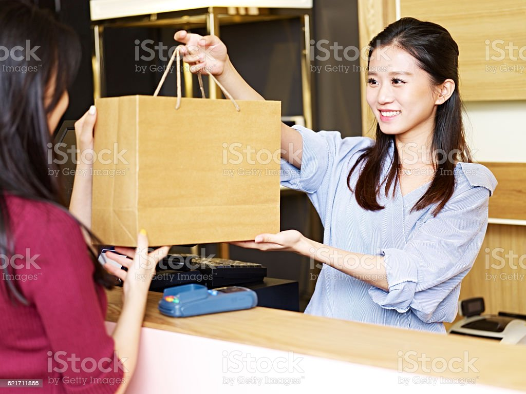 salesclerk handing merchandise to customer stock photo
