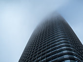 A skyward view of Salesforce Tower cutting the fog in San Francisco