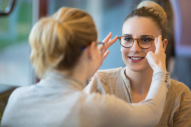 salesgirl assisting customer to in wearing glasses - optometrist stock pictures, royalty-free photos & images