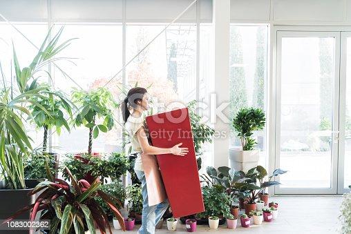 istock Saleslady carrying huge flowerpot 1083002362